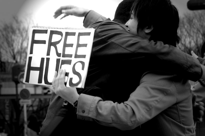 two+people+hugging+as+one+holds+a+sign+saying+%22free+hugs%22